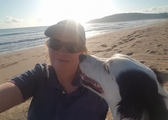 debbie the dog trainer with a black and white dog on the beach